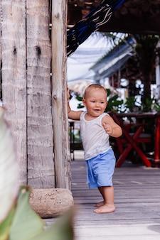 Outdoor portret van gelukkig negen maanden oud kind in blauw korte en witte overhemd staat door houten muur en glimlach