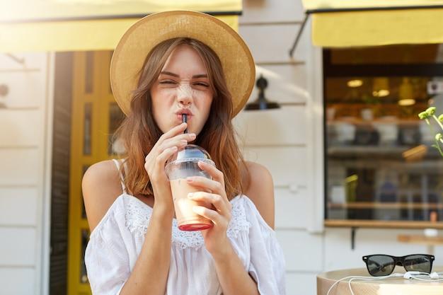 Outdoor portret van gelukkig schattige jonge vrouw draagt stijlvolle zomerhoed en witte jurk, voelt zich ontspannen, glimlachend en afhaalmaaltijden koffie drinken op straat in de stad