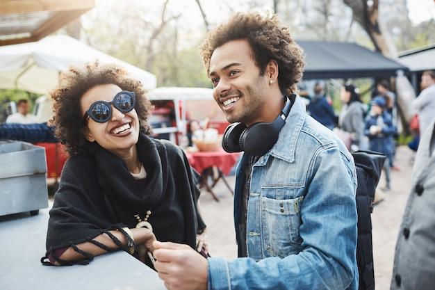 Outdoor portret van gelukkige afro-amerikaanse echtpaar met afro kapsels, leunend op tafel terwijl op food festival, genieten van tijd samen doorbrengen en wachten op hun bestelling.
