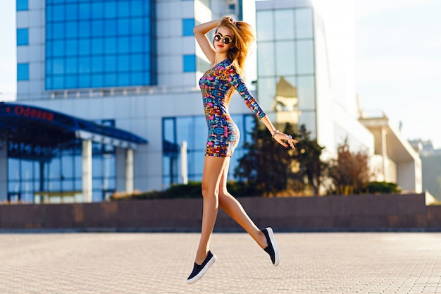 Outdoor portret van geweldige blonde vrouw heldere mini jurk, city fashion streetstyle dragen. felle kleuren.