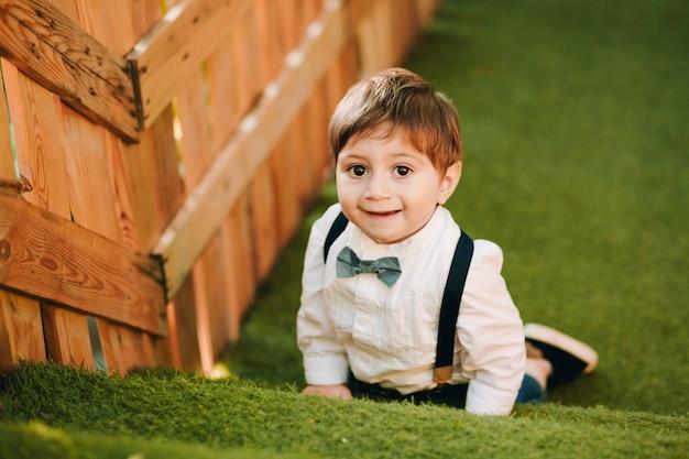 Outdoor portret van grappige kleine jongen liggend op kunstgras in de speeltuin en glimlachen