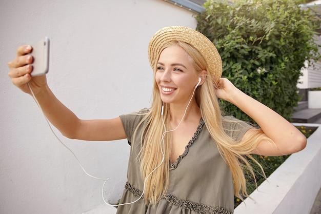 Outdoor portret van jonge gelukkig blonde vrouw selfie maken met haar smartphone, casual linnen jurk en strooien hoed dragen, op zoek gelukkig en vrolijk