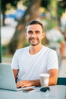 Outdoor portret van jonge lachende europese man zit in café met zijn laptop