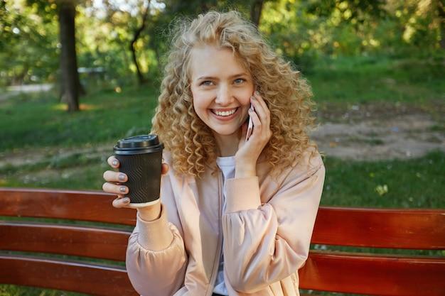Outdoor portret van jonge mooie vrouw blonde zit op een bankje, koffie drinken, spreken met iemand aan de telefoon