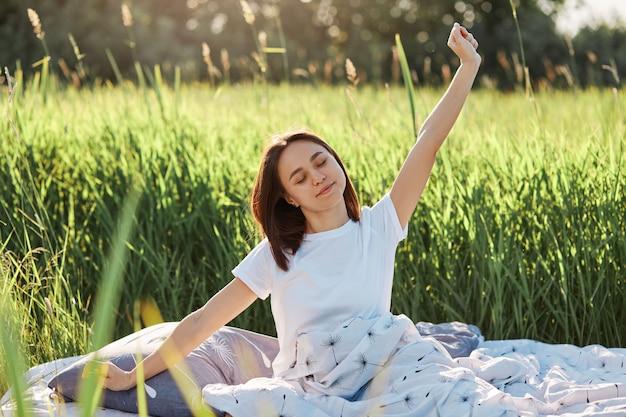 Outdoor portret van jonge volwassen slaperige vrouw met donker haar zittend in zacht linnen in groen veld, wordt wakker in de weide, houdt de ogen gesloten, strekt de handen uit na het slapen.