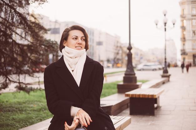 Outdoor portret van kaukasische vrouw, gekleed in zwarte winterjas en sjaal zittend op de bank, stad op achtergrond