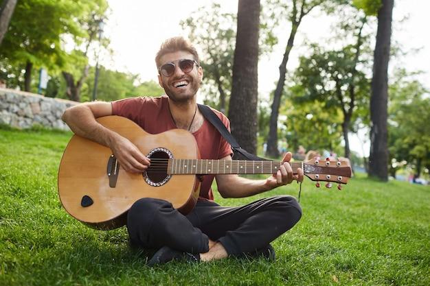 Outdoor portret van knappe hipster man zittend op het gras in het park en gitaar spelen