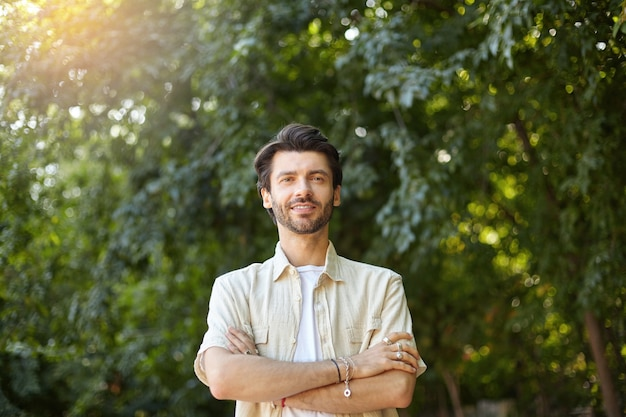 Outdoor portret van knappe jonge bebaarde man in beige overhemd poseren met gekruiste handen op zijn borst, op zoek met een lichte glimlach