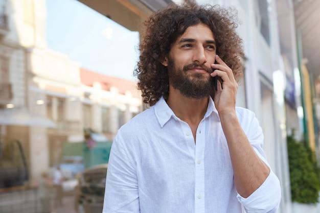 Outdoor portret van knappe jonge krullende man met weelderige baard, praten over de mobiele telefoon tijdens de lunchpauze, gekleed in een wit overhemd