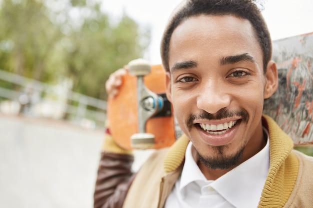 Outdoor portret van knappe man met donkere ogen, baard en snor, houdt skateboard achter het hoofd