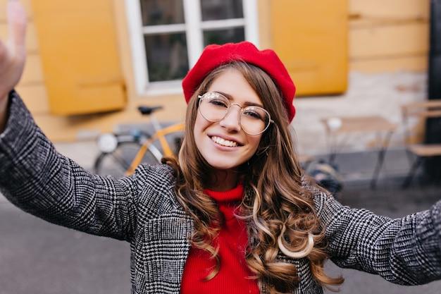 Outdoor portret van lachen romantische dame in glazen selfie maken voor geel gebouw