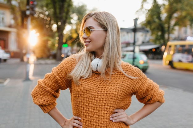 Outdoor portret van lachende blonde vrouw met trendy manicure wegkijken genieten van uitzicht op de stad