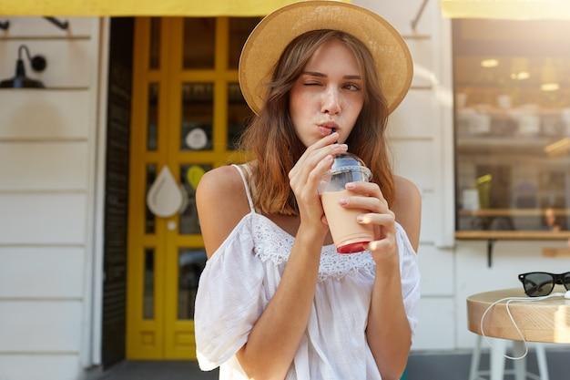 Outdoor portret van lachende speelse jonge vrouw draagt stijlvolle hoed en witte zomerjurk, voelt zich gelukkig, knipogen en milkshake drinken op straat in de stad
