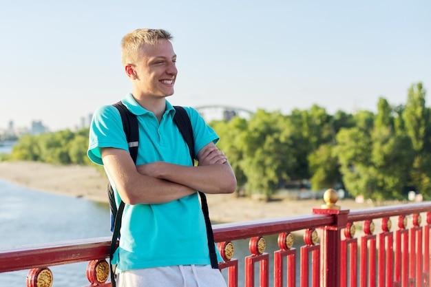 Outdoor portret van lachende tiener 15, 16 jaar oud met gekruiste armen. mannetje op brug over rivier op zonnige zomerdag, kopieer ruimte