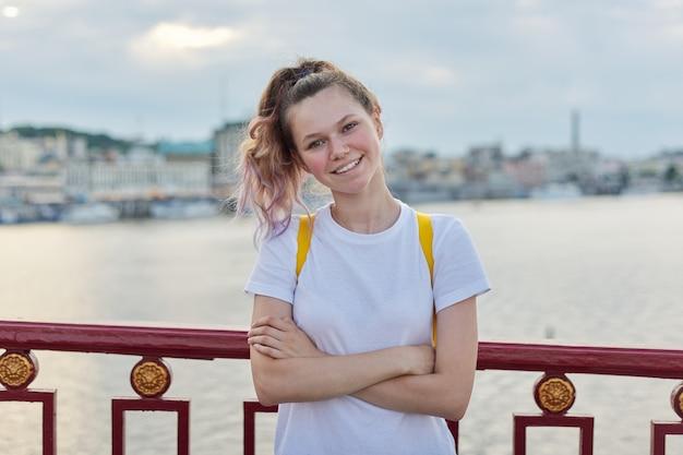 Outdoor portret van lachende tienermeisje van 15, 16 jaar oud met gevouwen armen, rugzak kijken naar de camera. meisje staande op de brug, zonsondergang rivier achtergrond