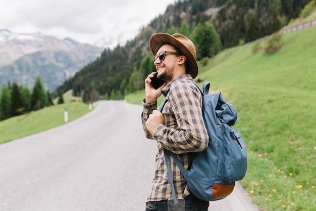 Outdoor portret van man met smartphone in de hand lopend op de weg met blauwe rugzak