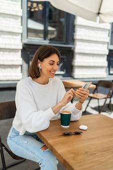 Outdoor portret van mooie kortharige vrouw genieten van cappuccino in café, gezellige witte trui dragen, luisteren naar favoriete muziek via oortelefoons en chatten via mobiele telefoon.