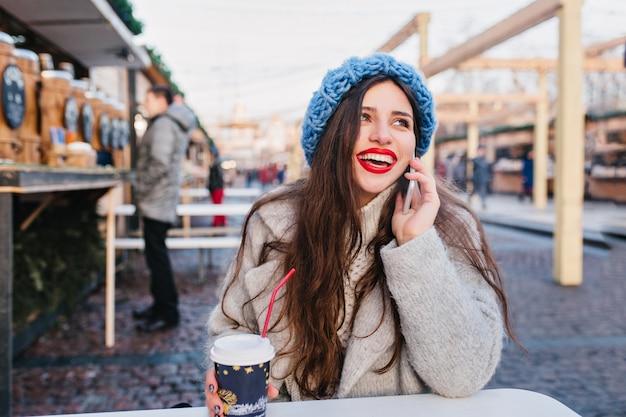 Outdoor portret van opgewonden brunette meisje in wollen jas genieten van winterweekend in warme dag. foto van langharige blanke dame in schattige blauwe hoed poseren op straat vervagen