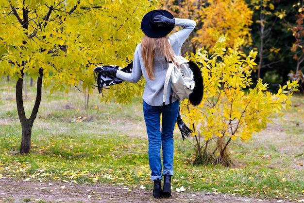Outdoor portret van opgewonden meisje draagt trendy brede rand en staat in zelfverzekerde pose. aantrekkelijke jonge vrouw in glazen poseren op herfst natuur achtergrond.