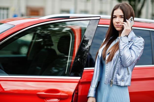Outdoor portret van prachtige vrouw poseren in de buurt van oranje suv auto met open deur, spreekt op de telefoon,