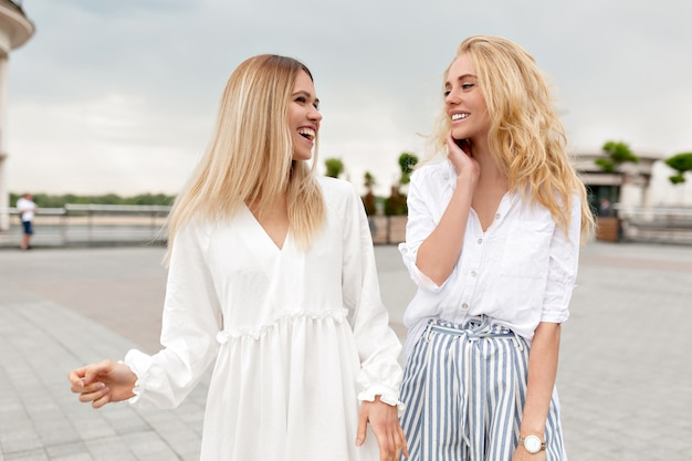 Outdoor portret van schattige dames plezier buiten ontspannen in de zomer stad tijdens het wandelen op straat en lachen op bewolkte zomerdag. twee stijlvolle meisjes buiten