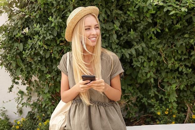 Outdoor portret van schattige jonge blonde vrouw in casual linnen jurk over groene tuin, smartphone in handen houden en opzij kijken met een brede glimlach