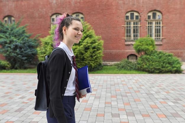 Outdoor portret van schoolmeisje in de buurt van schoolgebouw, mooie trendy tiener meisje met rugzak naar school, kopie ruimte