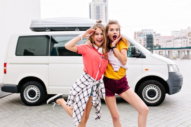 Outdoor portret van slanke stijlvolle vrienden grappig poseren naast witte auto met glimlach en verbaasd gezicht expressie