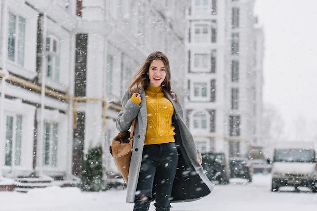 Outdoor portret van spectaculaire dame in gele trui op straat in warme winterdag. foto van tevreden modieuze vrouw in grijze vacht die zich onder sneeuwval op stedelijke straat bevindt.