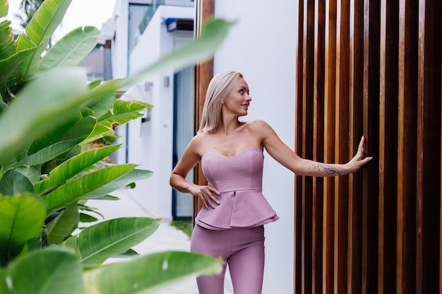 Outdoor portret van stijlvolle europese vrouw op roze mode pak buiten villa