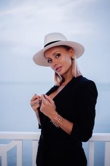 Outdoor portret van stijlvolle vrouw in zwart blazerkostuum en witte klassieke hoed