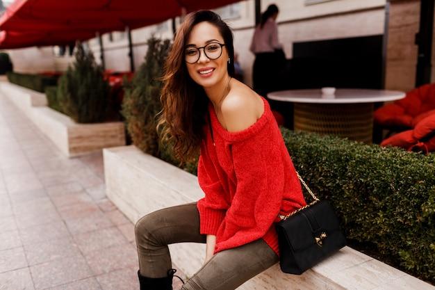 Outdoor portret van succesvolle lachende brunette vrouw in trendy rode gebreide trui zitten en genieten van europese feestdagen. elegante zwarte tas.