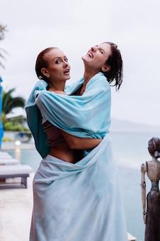 Outdoor portret van twee gelukkige vrouw in bikini met strandlakens op vakantie buiten villa bij zwembad op regenachtige dag