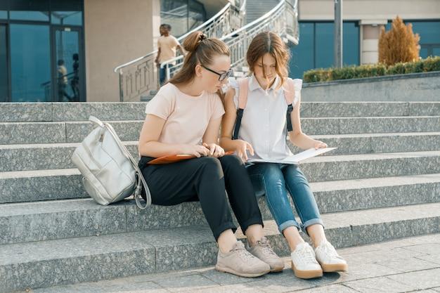 Outdoor portret van twee jonge mooie meisjes studenten met rugzakken