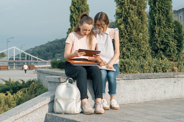 Outdoor portret van twee jonge mooie meisjes studenten