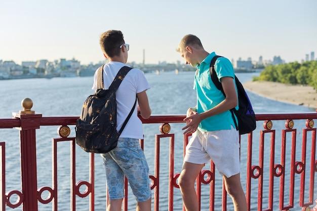 Outdoor portret van twee vrienden tieners jongens 15, 16 jaar oud, lachen, praten in zonnige dag, staande op de brug over de rivier. stedelijke levensstijl, tieners, vriendschap, communicatie