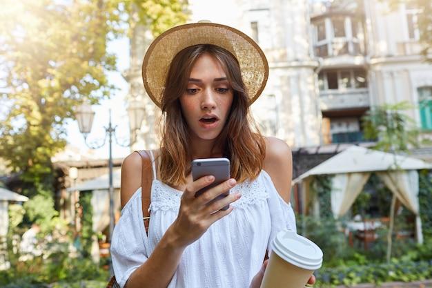 Outdoor portret van verbaasd mooie jonge vrouw draagt stijlvolle hoed en witte zomerjurk, voelt zich verrast, met behulp van smartphone en afhaalmaaltijden koffie drinken in de oude stad