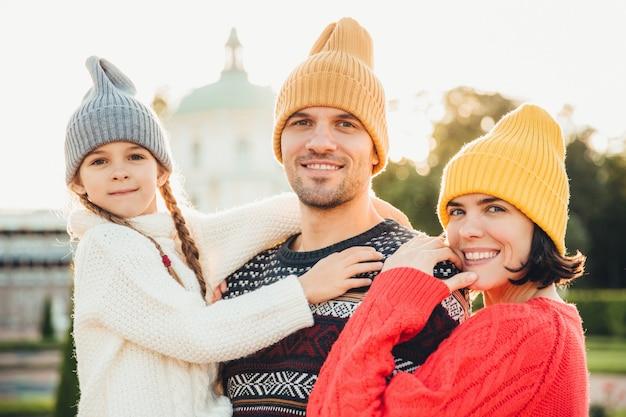 Outdoor portret van vriendelijke familie staan dicht bij elkaar, hebben een brede glimlach