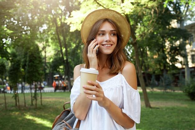 Outdoor portret van vrolijke aantrekkelijke jonge vrouw draagt stijlvolle hoed, voelt zich gelukkig, staande en afhaalmaaltijden koffie drinken in de stad in de zomer
