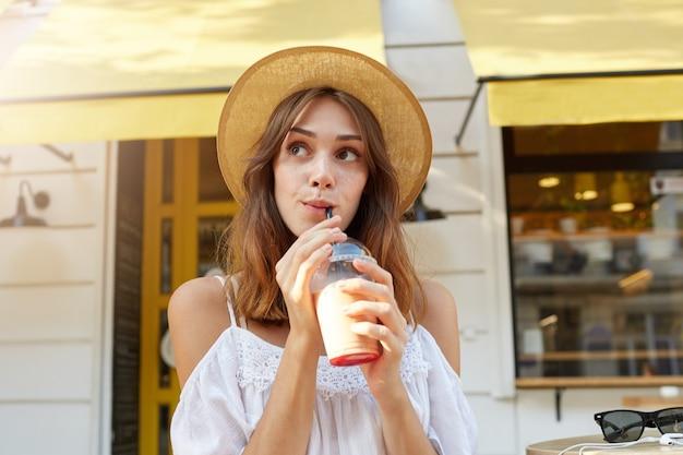 Outdoor portret van vrolijke charmante jonge vrouw draagt stijlvolle zomerhoed en witte jurk, voelt zich ontspannen, staande en afhaalmaaltijden koffie drinken op straat in de stad