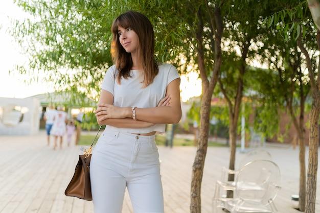 Outdoor portret van vrolijke vrouw in wit t-shirt en spijkerbroek wandelen in het park.