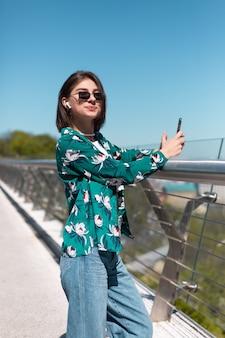 Outdoor portret van vrouw in casual groen shirt op zonnige dag staat op brug kijken op telefoon scherm draadloze bluetooth hoofdtelefoon in oren