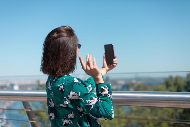 Outdoor portret van vrouw in casual groen shirt op zonnige dag staat op brug kijken op telefoonscherm nemen selfie videogesprek draadloze bluetooth koptelefoon in oren