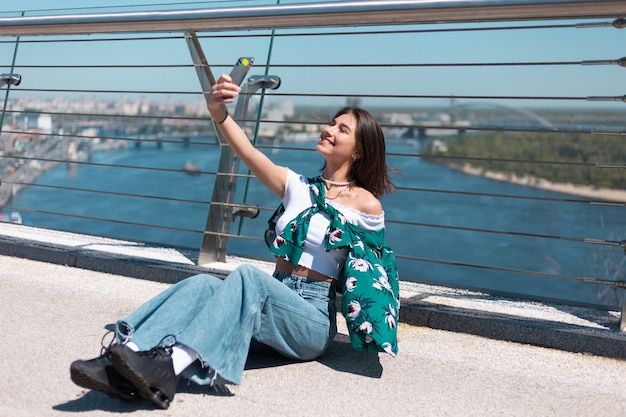 Outdoor portret van vrouw in casual groen shirt op zonnige dag staat op brug kijken op telefoonscherm nemen selfie videogesprek