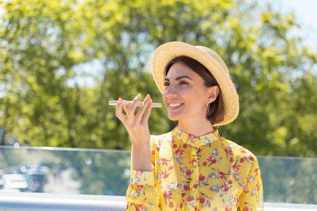 Outdoor portret van vrouw in gele zomerjurk en hoed audio spraakbericht opnemen op de telefoon