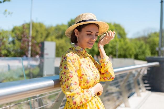Outdoor portret van vrouw in gele zomerjurk en hoed luisteren audio spraakbericht op telefoon, staat op de brug met prachtig uitzicht op de stad