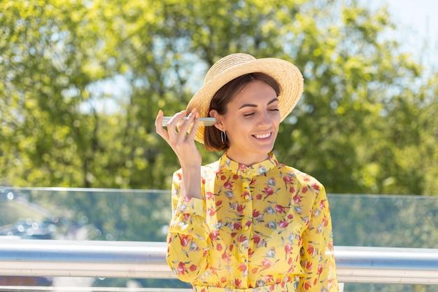 Outdoor portret van vrouw in gele zomerjurk en hoed luisteren audio spraakbericht op telefoon