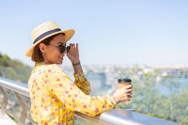 Outdoor portret van vrouw in gele zomerjurk en hoed met kopje koffie genieten van zon, staat op brug met prachtig uitzicht op de stad