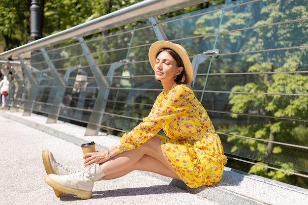 Outdoor portret van vrouw in gele zomerjurk en hoed met kopje koffie genieten van zon