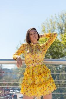 Outdoor portret van vrouw in gele zomerjurk poseren op brug, gelukkig vrolijke stemming, genieten van zonnige zomerdagen
